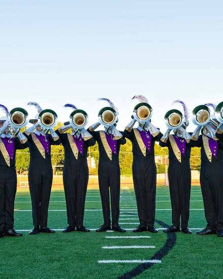 Marching band members posing with their instruments on a football field.